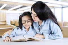 Insegnante che legge un libro con il suo studente Fotografia Stock