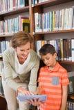 Insegnante che mostra compressa all'allievo alla biblioteca Immagine Stock