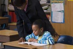 Insegnante che osserva sopra la spalla dell'allievo Fotografia Stock Libera da Diritti