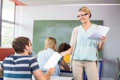 Insegnante che passa carta allo studente nella classe Fotografie Stock