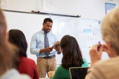 Insegnante che per mezzo del computer della compressa ad una classe di corsi per adulti Immagini Stock