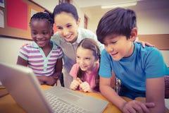 Insegnante che per mezzo del computer portatile con gli allievi Fotografia Stock Libera da Diritti