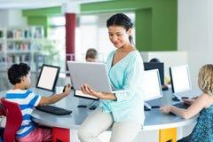 insegnante che per mezzo del computer portatile con la classe del computer Fotografia Stock Libera da Diritti