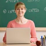 Insegnante che propone con il computer portatile nell'aula del banco Fotografia Stock Libera da Diritti