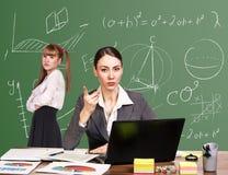 Insegnante che si siede allo scrittorio Immagine Stock Libera da Diritti