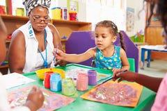 Insegnante che si siede con i bambini in una classe prescolare, fine su Fotografie Stock