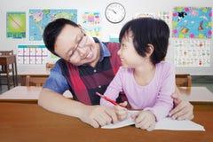 Insegnante che sorride ad una studentessa Fotografia Stock