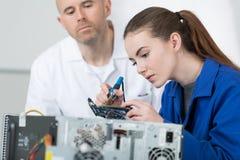 Insegnante che sorveglia il giovane tecnico femminile del computer Fotografie Stock