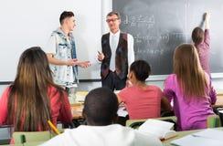 Insegnante che spiega il per la matematica vicino alla lavagna Immagini Stock Libere da Diritti
