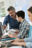 Insegnante con gli apprendisti nella classe di calcolo Immagini Stock Libere da Diritti