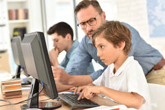 Insegnante con i bambini che per mezzo del computer Immagini Stock Libere da Diritti