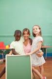 Insegnante con i suoi studenti che tengono una lavagna Fotografie Stock Libere da Diritti