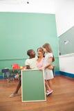 Insegnante con i suoi studenti che tengono una lavagna Fotografia Stock