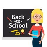 Insegnante con i vetri ed il libro e di nuovo alla lavagna della scuola Immagine Stock
