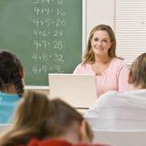Insegnante con il computer portatile in aula Fotografie Stock