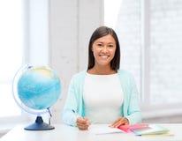 Insegnante con il globo ed il blocco note alla scuola Fotografie Stock