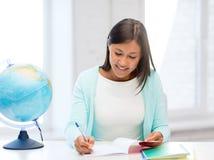 Insegnante con il globo ed il blocco note alla scuola Fotografia Stock