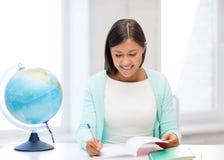 Insegnante con il globo ed il blocco note alla scuola Immagini Stock