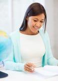 Insegnante con il globo ed il blocco note alla scuola Immagine Stock