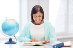Insegnante con il globo ed il libro alla scuola Fotografia Stock Libera da Diritti