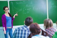 Insegnante con il gruppo di allievi in aula Immagine Stock