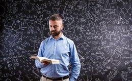Insegnante con il libro contro la grande lavagna con i simboli e il formul Immagini Stock Libere da Diritti