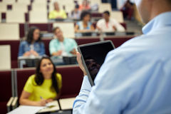 Insegnante con il pc e gli studenti della compressa alla conferenza Immagine Stock