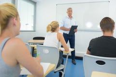 Insegnante con la lavagna per appunti negli studenti anteriori della classe Immagine Stock