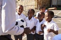 Insegnante con la palla e bambini nel campo da giuoco della scuola elementare Fotografia Stock
