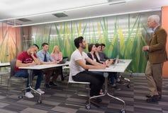 Insegnante con un gruppo di studenti in aula Immagine Stock