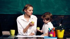 Insegnante con un ragazzino che mangia mela ad una tavola dell'allievo e che conta contro un fondo di un consiglio scolastico ver archivi video