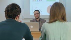 Insegnante d'ascolto degli allievi in aula Immagini Stock