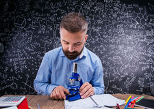 Insegnante dei pantaloni a vita bassa allo scrittorio con il microscopio, grande lavagna Immagine Stock