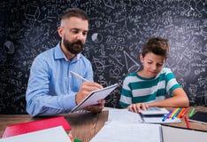 Insegnante dei pantaloni a vita bassa con il suo studente con il calcolatore, grande lavagna Immagine Stock
