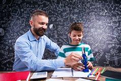 Insegnante dei pantaloni a vita bassa con il suo studente con il microscopio, grande lavagna Fotografie Stock Libere da Diritti