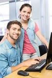 Insegnante del computer che aiuta studentessa graziosa Fotografia Stock
