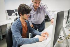 Insegnante del computer che assiste uno studente immagine stock