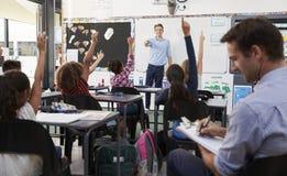 Insegnante dell'apprendista che impara come insegni agli studenti elementari Immagini Stock