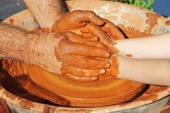 Insegnante dell'officina del lavoro delle terraglie della ruota di mani del vasaio e piccolo allievo Immagine Stock