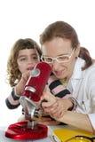 Insegnante della donna del medico e microscopio della pupilla Fotografie Stock