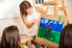 Insegnante di arte che aiuta uno studente Immagini Stock