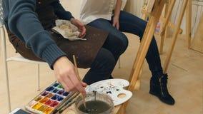 Insegnante di arte ed il suo apprendista che lavorano ad un'immagine dell'acquerello Fotografia Stock