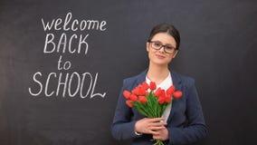Insegnante di signora che sorride e che tiene mazzo di tulipani, benvenuto di nuovo a scuola scritta video d archivio