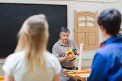 Insegnante di una classe della lavorazione del legno che insegna a due studenti Immagini Stock