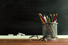 Insegnante di vetro e un supporto con le matite sulla tavola, sui precedenti di una lavagna con gesso Il concetto del ` s dell'in Fotografie Stock