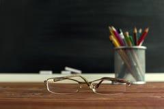 Insegnante di vetro e un supporto con le matite sulla tavola, sui precedenti di una lavagna con gesso Il concetto del ` s dell'in Fotografie Stock Libere da Diritti