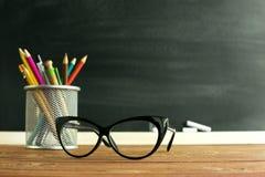 Insegnante di vetro e un supporto con le matite sulla tavola, sui precedenti di una lavagna con gesso Il concetto del ` s dell'in Fotografia Stock Libera da Diritti
