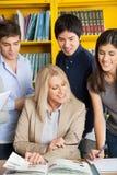 Insegnante Discussing With Students alla Tabella dentro Fotografie Stock Libere da Diritti
