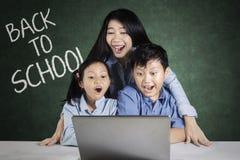 Insegnante e bambini con il computer portatile nella classe Immagine Stock