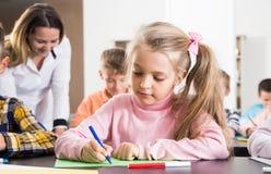 Insegnante e bambini elementari di età che disegnano all'aula Fotografie Stock